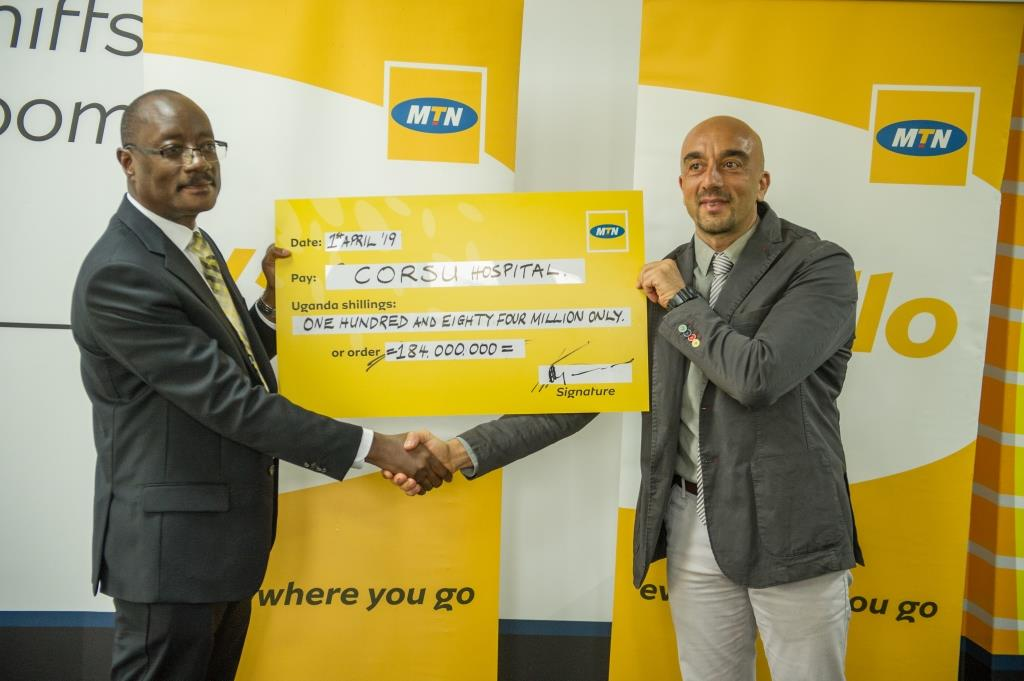 (L-R) Acting MTN Uganda CEO Mr. Gordian Kyomukama hands over a UGX 184m cheque to improve the quality of life for children with disabilities to CoRSU Hospital CEO Dr. Davide Naggi