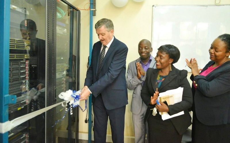 The Irish Ambassador to Uganda, H.E. William Carlos (Left) cuts the tape to mark the official launch of four new innovation labs under netLabs!UG as Deputy Principal CEDAT-Dr. Venny Nakazibwe (2nd R), PI netLabs!Ug- Eng. Dr. Dorothy Okello (R) and a netLabs!UG official applaud.