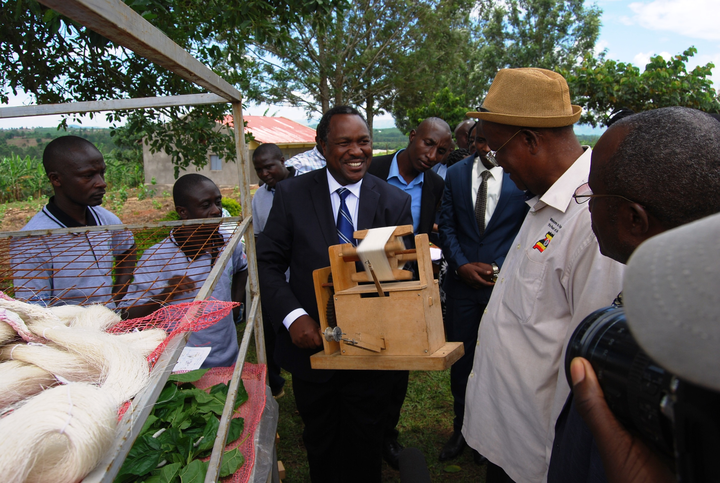 Minister Elioda Tumwesigye(C) demonstrating how thread  are made under sericulture as minister Kamuntu looks on. (Photo by BOB AINE)