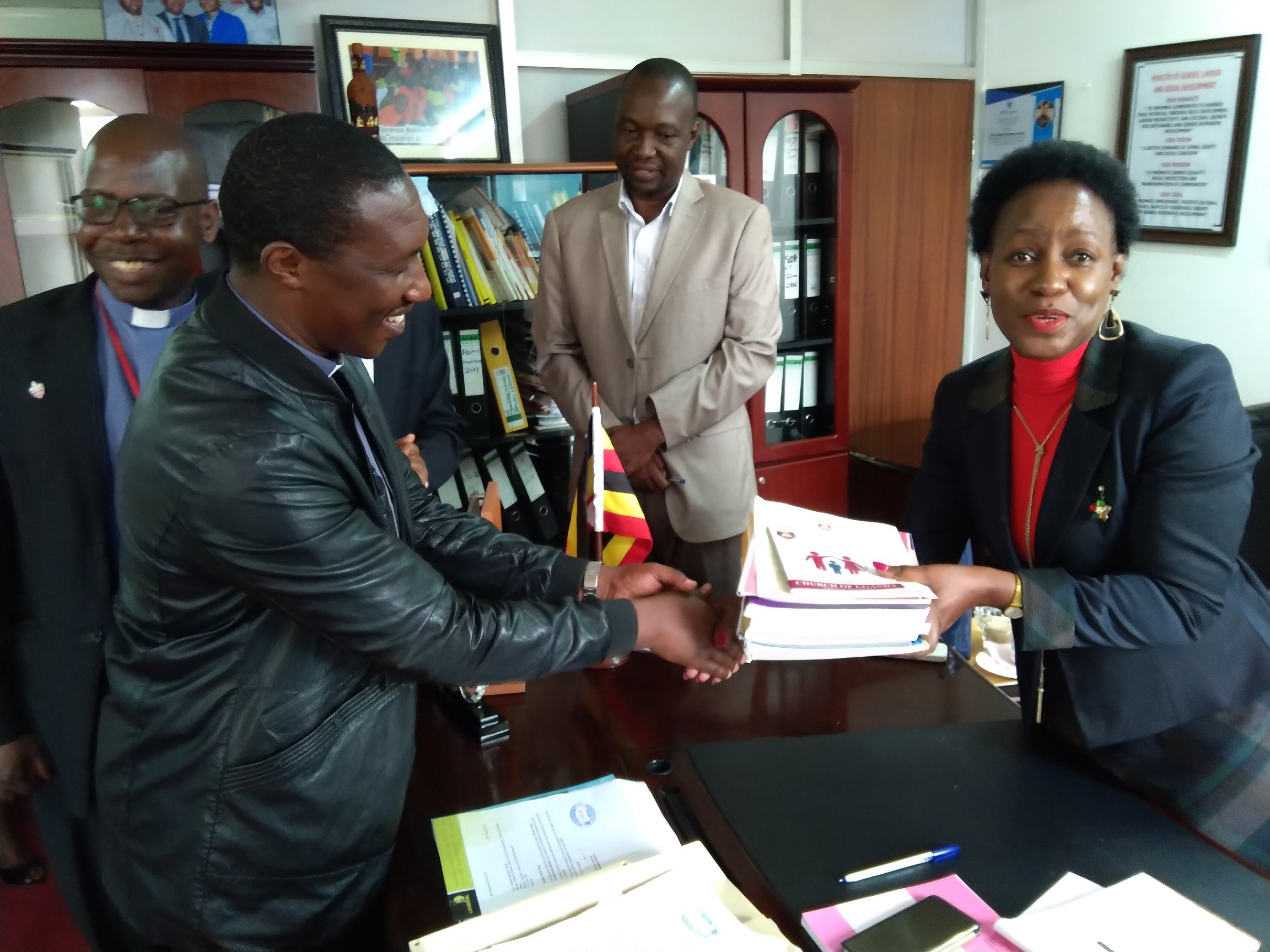 Minister of State for Youth and Children Hon Florence Nakiwala Kiyingi (right) receives CoU manuals and policy documents on children from Rev Richar