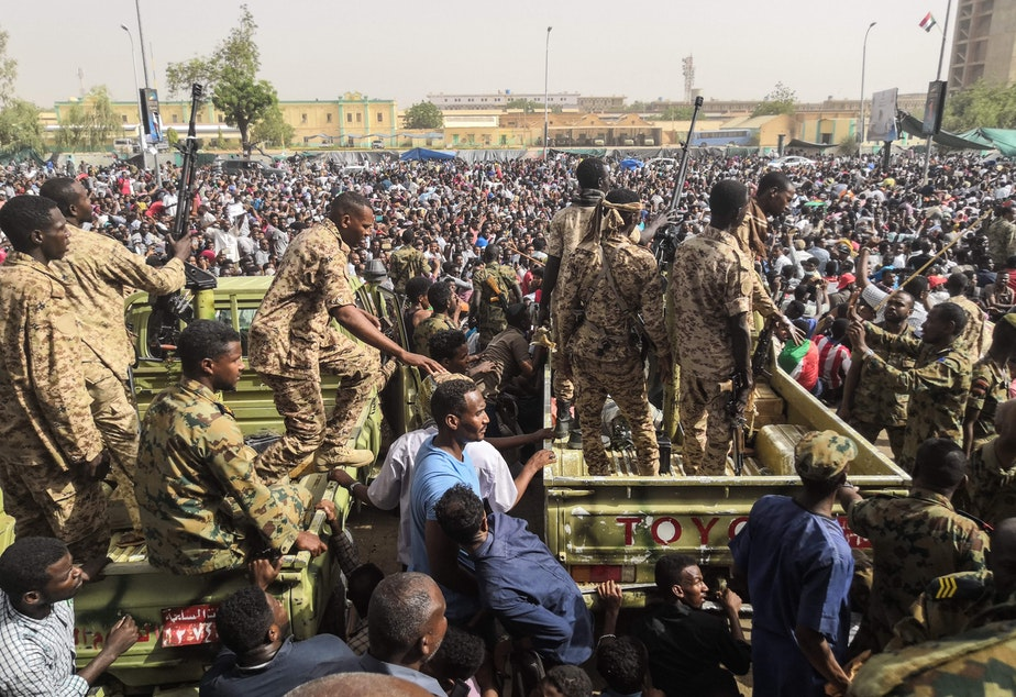 Sudanese soldiers stand guard on armored vehicles as demonstrators protest against President Omar al-Bashir's