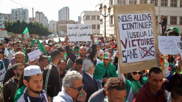"""Demonstrators carried signs protesting against the ruling elite on Friday, including one saying """"We are going to continue to victory without you"""""""
