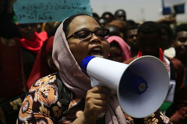 A Sudanese woman speaks through a loudspeaker as demonstrators gather during a rally near the military headquarters in the capital Khartoum on April 16, 2019. Protesters in Sudan toughened their stance Sunday June 30, dubbed the 'Millions march'. (PHOTO/Agencies)