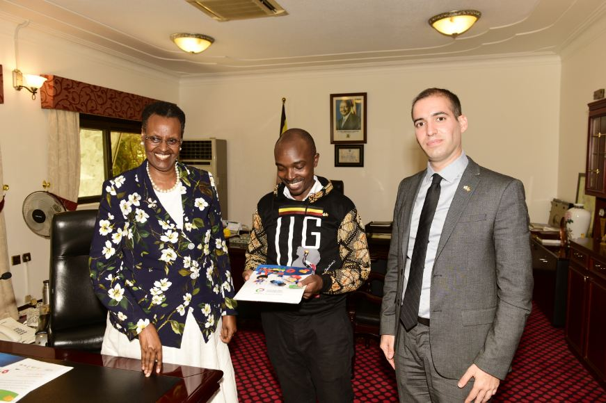 Arinaitwe Rugyendo (M) shows First LAdy Janet Museveni (L) a cpy of the Young Engineers Profile. On the Right is H.E Eyal David. (PHOTO/Courtesy)