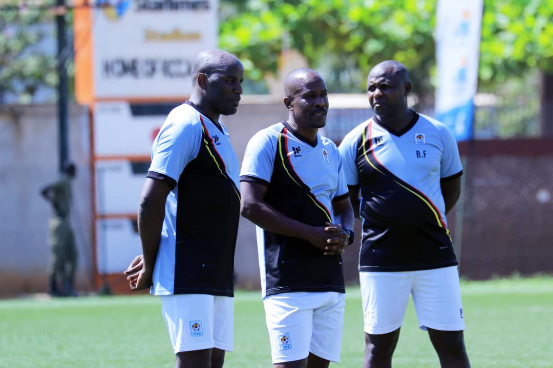 Mubiru (C) shares a moment with his technical team on Tuesday. (Photo/FUFA)