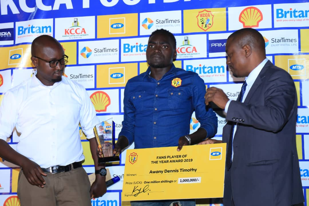 Awanyi (C) displays his plaque and check after he was named KCCA FC's MVP. (PHOTOS/KCCA FC)