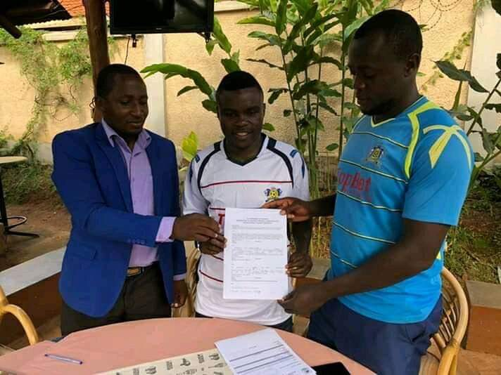 Gadaffi (center) poses for a picture with Mbarara City officials after signing for the Ankole Lions on Thursday. (PHOTO/AGENCY)