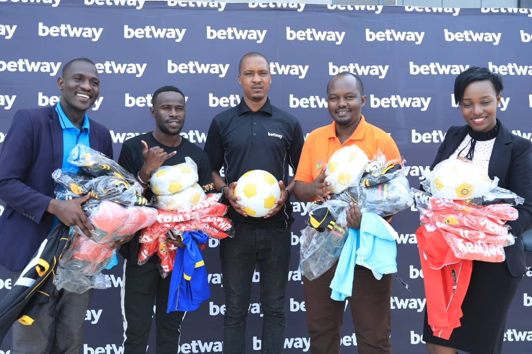 Betway PR Clive Kyazze (Center) hands over the items to KDFC officials on Tuesday.
