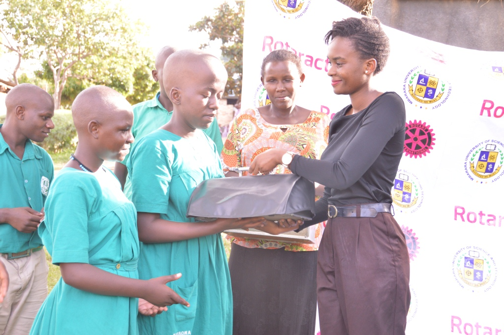 Pupils recieving machines from a member of the rotaract club of MUST