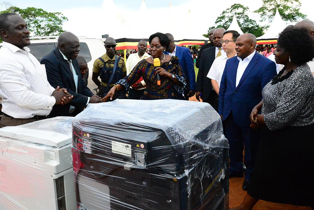 The Speaker of Parliament, Rebecca Kadaga, handing over printing equipment to Mbulambuti Primary School. (PML PHOTO)