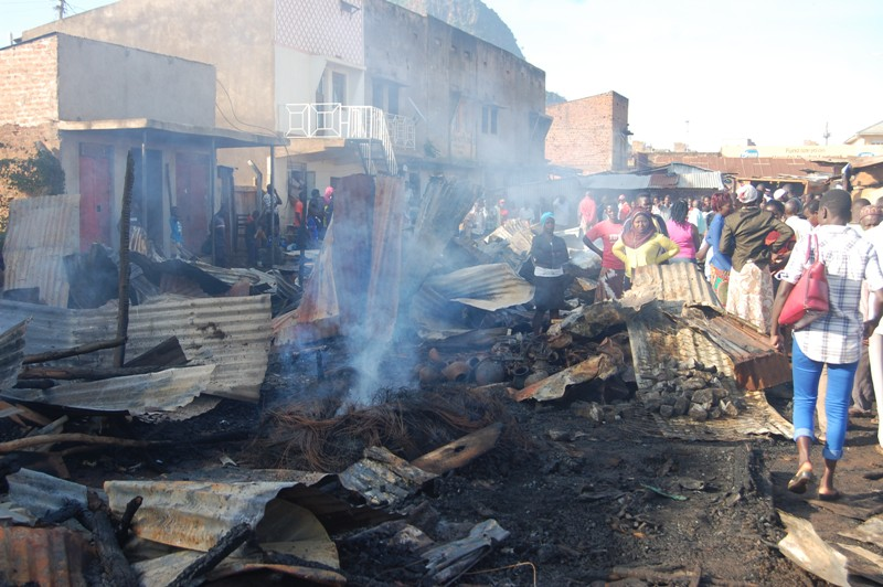 Traders and members of the public stand to sympathizing with burnt market stalls at Tororo market. Photo by Joseph Omollo