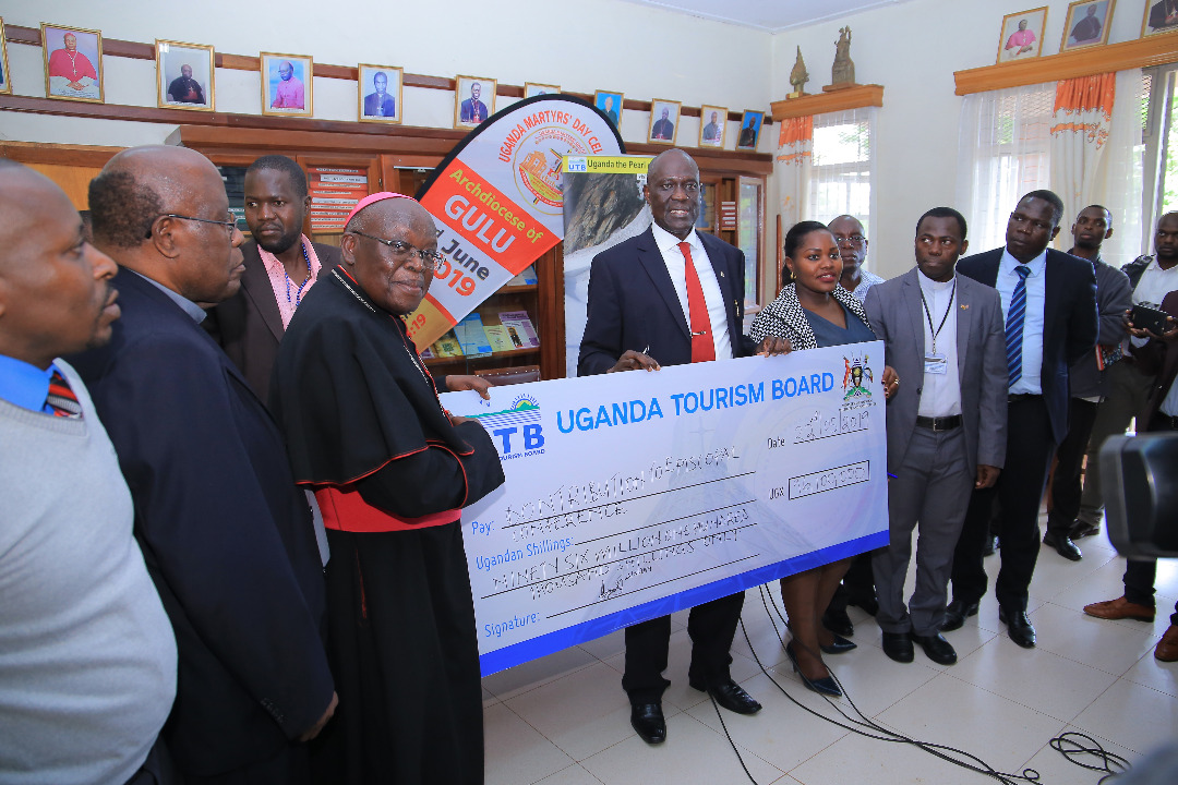 Mr. Bradford Ochieng hands over a dummy cheque to Gulu Archbishop John Baptist Odama after  both addressed the press on May 23 (PHOTO/PML Daily)