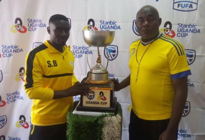 The two head coaches, Proline's Shafick Bisaso (left) and Bright Stars' Fred Kajoba (right) have a feel of the Uganda Cup trophy ahead of the final on Saturday. (PHOTOS/FILE)