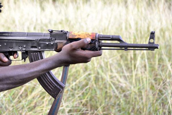 A man holds an AK47