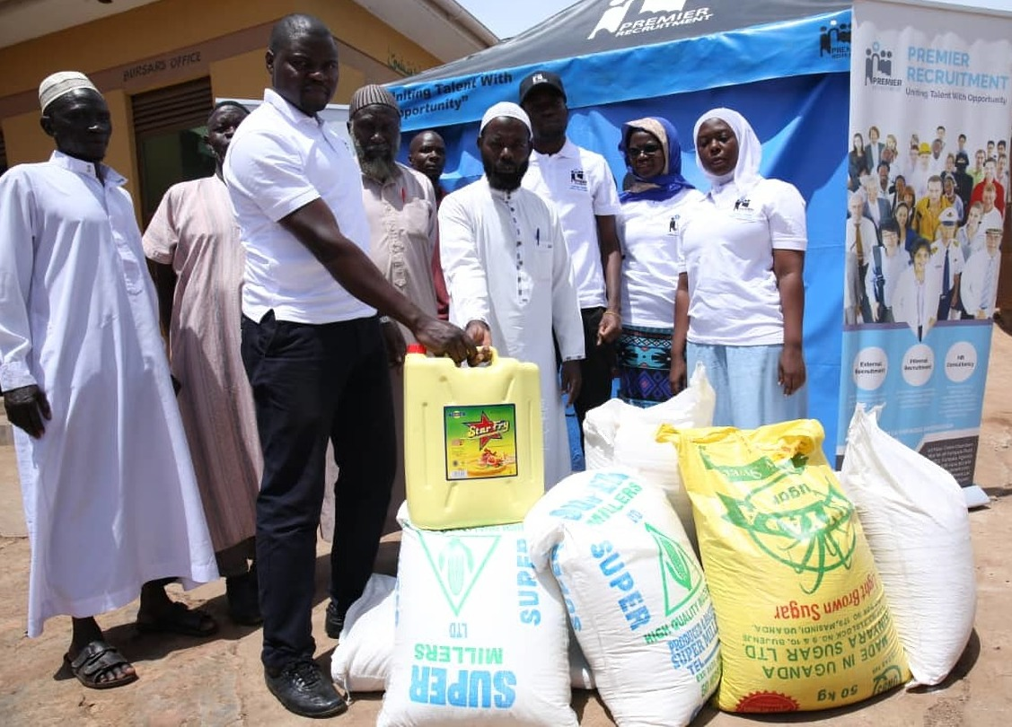 Premier Recruitment Staff handing over foodstuff to the Muslim Community in Bwaise, a Kampala surburb.  (PHOTO/ Abraham)