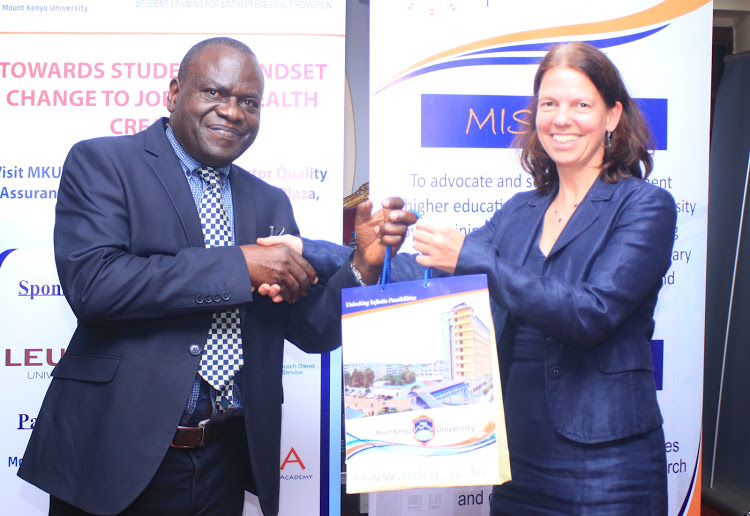 Mount Kenya University VC Stanley Waudo presents a gift to head of Culture and Education at the German Embassy Madam Ursula Koos on MKU Thika campus on April 30  Image: COURTESY