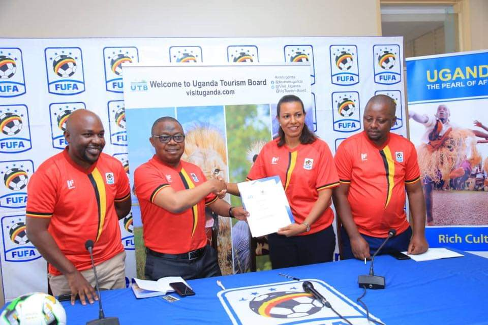 FUFA First Vice President Justus Mugisha show off the MOU with Uganda Tourism Board's CEO Lily Ajarova. (PHOTOS/FUFA).