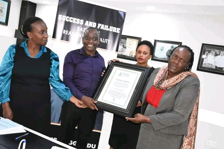 L - R .  Ms. Angella Kyagaba, senior curriculum specialist at the National Curriculum Development Centre,  Mr. Hamis Kiggundu,Author Success and Failure  Based on Reason and Reality receiving a Certificate  Recognition from  Grace Baguma, director at the National Curriculum Centre  after the book was introduced on the Curriculum ( Photo /Abraham Mutalyebwa).