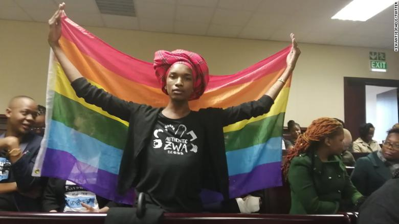 a woman holds a LGBTQ flag inside Botswana's High Court on Tuesday, where lawmakers overturned a law that criminalized same-sex relations.