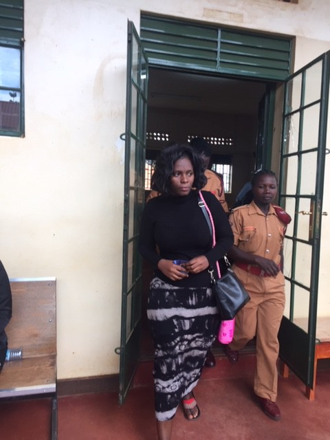 Ms. Nakku leaving court with a prison warden after the court session. (PHOTO/Elizabeth Namajja)