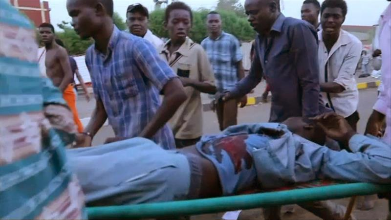 An image grab taken from a Facebook video shows Sudanese protesters carrying a wounded demonstrator during confrontation with security forces near Khartoum's army headquarters [Facebook Page of Ahmed Kwarte/AFP]