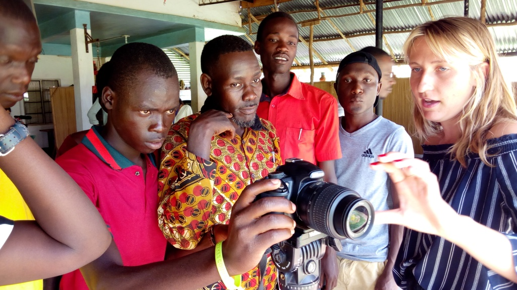 Foriegn Volunteer teaching youth how to operate video camera in Gulu.