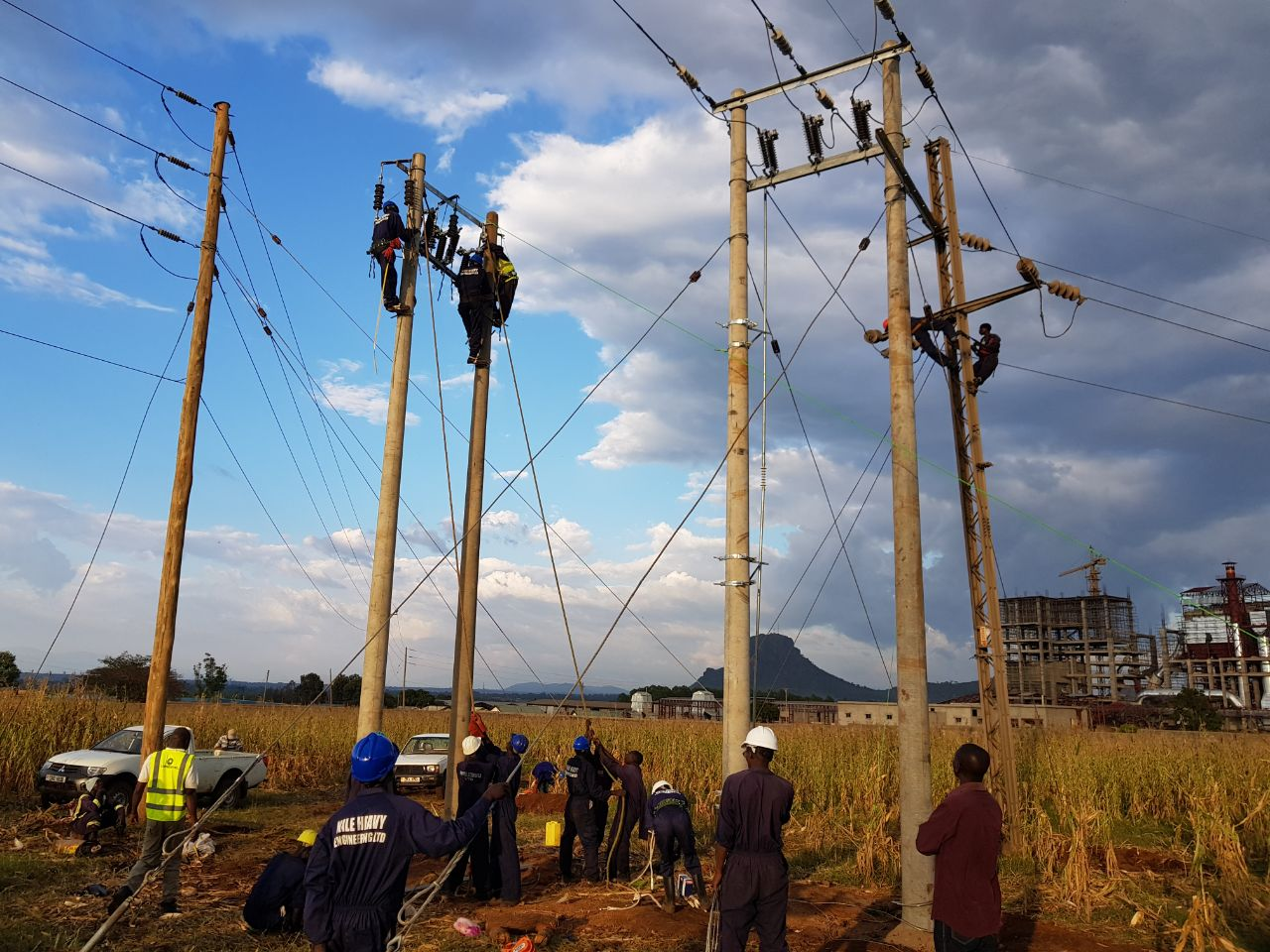 Staff of Uganda Electricity Transmission Company Limited (UETCL) mount a power line. (PHOTO/File)