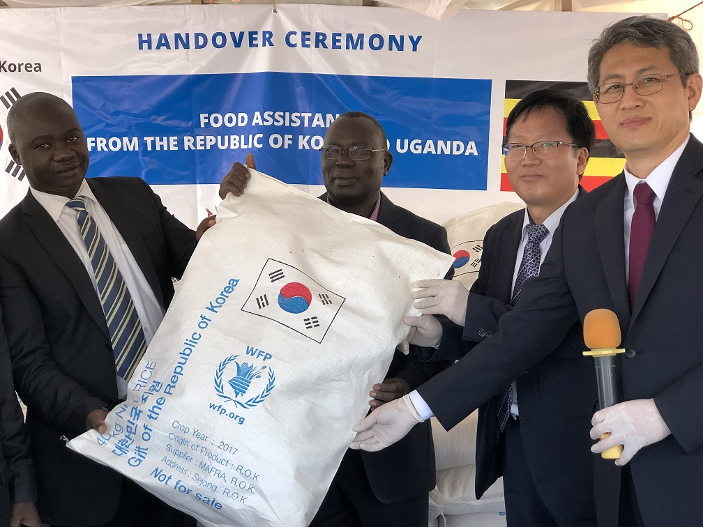The Korean Ambassador in Uganda (right) and another official hand over rice to Ugandan officials in Nakivale. Centre is the Commissioner for Refugees, Mr. Gerald  Mehnya.