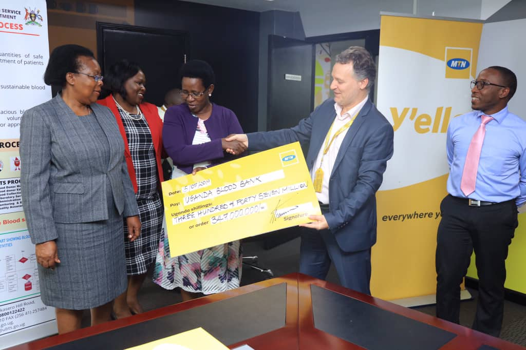 MTN Uganda CEO Wim hands over a dummy chequee worth UGX347Million to the PS Ministry of Health, Dr Atwiine Monday July 15. (PHOTO/PML Daily)