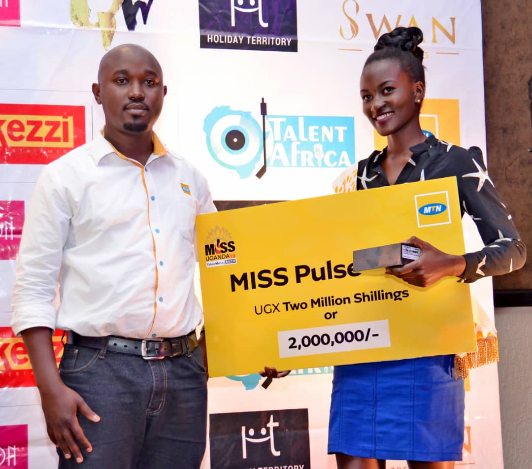 Bronnie Devine Kusiima receiving her dummy cheque of UGX2M and phone as Miss MTN Pulse / Popularity. (PHOTO/Abraham)