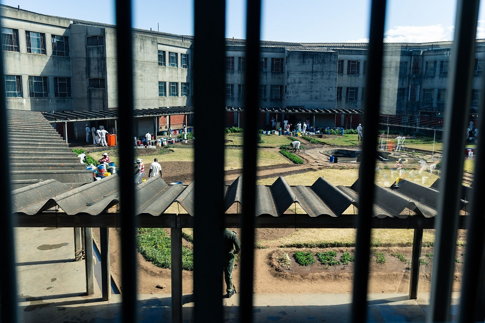 A Zimbabwe Prison Services (ZPS) officer (bottom) stands guard over the prison courtyard during a tour of Chikurubi Maximum Prison by a parliamentary committee on health who wanted to have an appreciation of key health and HIV issues facing persons in prison on June 13, 2019. - The Chikurubi Maximum Security Prison in Harare is crumbling at the seams, assailed by overcrowding and a critical shortage of medicines, food and other basics as the economically-crippled country battles to care for its inmates. (Photo by Jekesai NJIKIZANA / AFP)