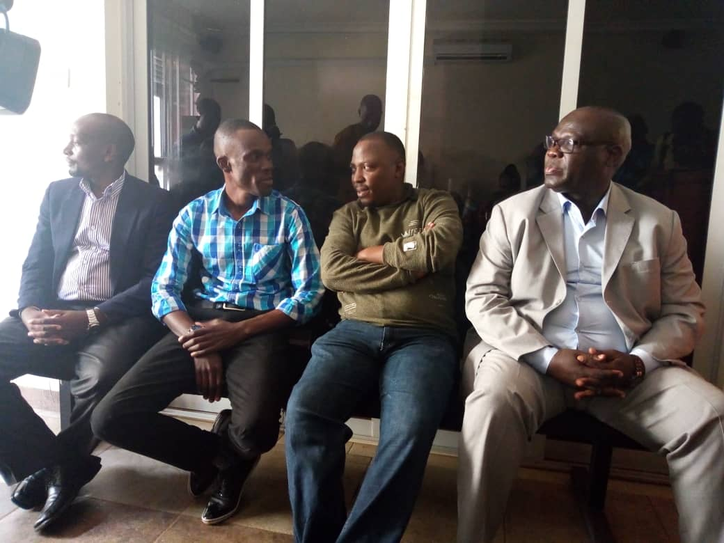 L-R Kwihangana Manasseh, Ronnie Kwesiga, Moses Mugabe and Mujuni Mpitsi in court awaiting for their charges to be read to them. Photo by Rachel Agaba.