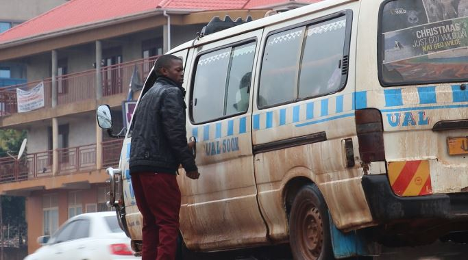 A commuter tax tout goes about his business. Taxi have become an item in the uncouth theft of  valuables in Kampala. (PHOTO/File)