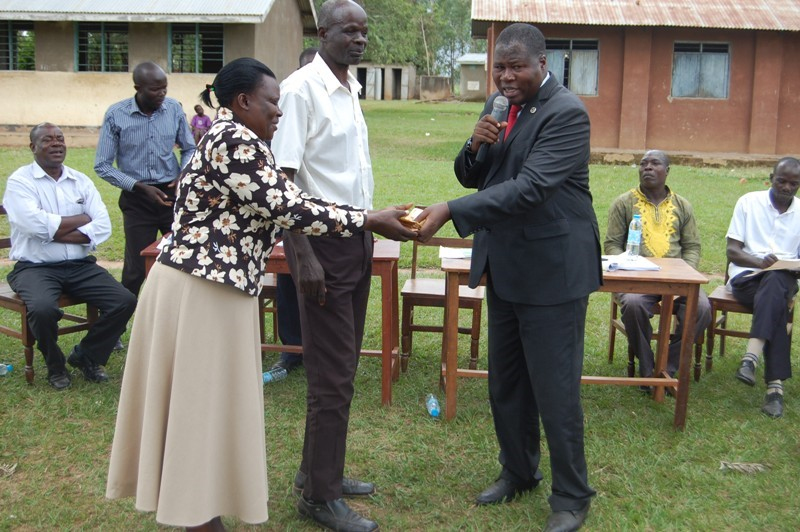 Budama South constituency MP Mr. Jacob Oboth hands over 3.5 millioon shillings to Katerema primray school head teacher anne Rose Athieno. (PHOTO/Joseph Omollo)