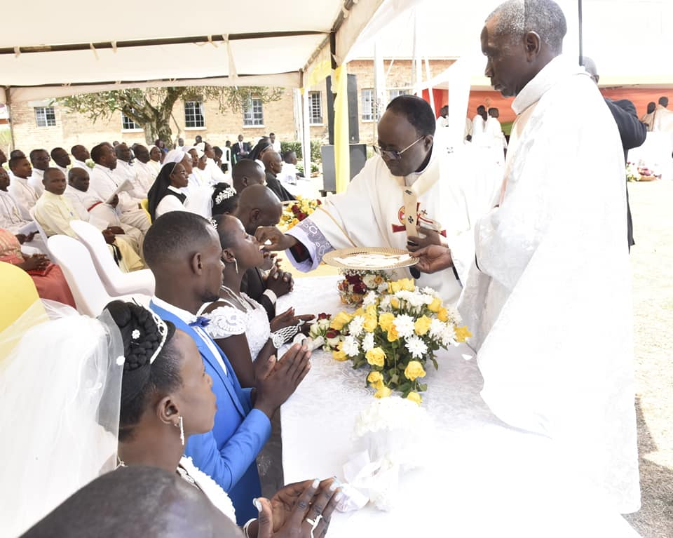Archbishop of Kampala Metropolitan Diocese Cyprian Kizito Lwanga, gives a couple the Holy Eucarist at the Commemoration mass. (PHOTO/George Okello)