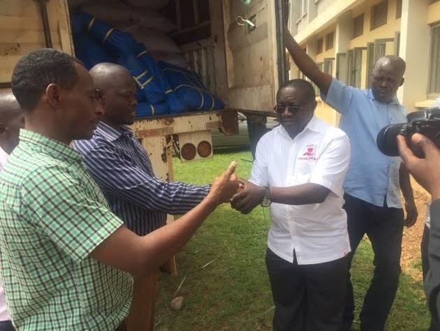 Assistant Chief Administrative Officer (CAO) Mr Kizito Mugerwa (white shirt) shakes hands with the Katooke sub county Chief Mr Moses Bwogi as the LCV Chairperson Mr Andrew Ssenyonga (green checked shirt) looks on at the Mukono District offices