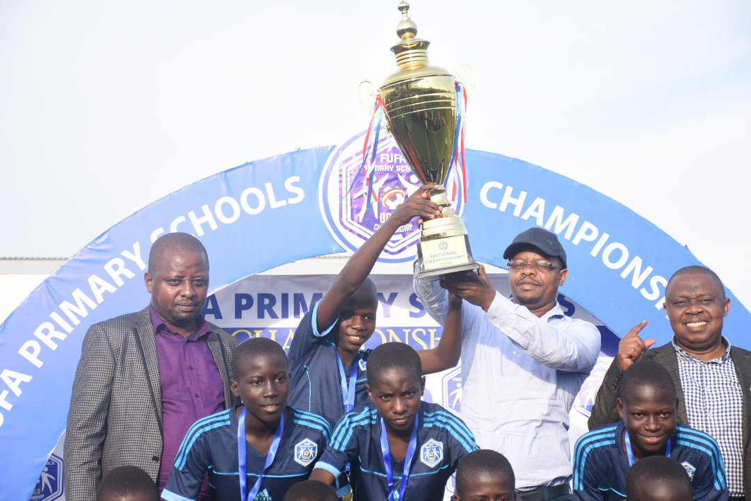 FUFA Predsident Moses Magogo (in white) hands over the winners' trophy to Rays of Grace captain Leornard Kasanya on Wednesday. (PHOTOS/FUFA)