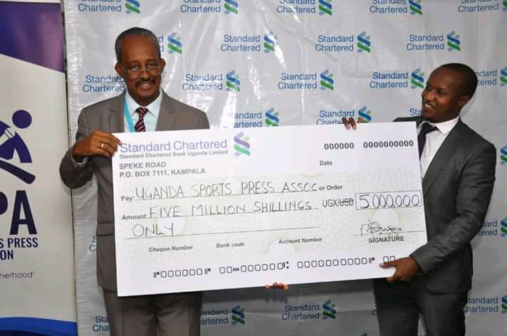 Standard Chartered's Edward Barlow (left), hands over the UGX 5m cheque to USPA President Patrick Kanyomozi (right), on Monday. (PHOTO/Courtesy)
