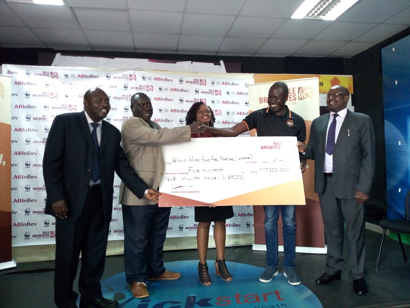 (L - R) Mr. Simon Weredwong Ag. country director World Wide Fund for Nature Uganda Country Office ( WWF- UCF) , Ambassador Dr. Philip Idro , the  Board chairman wide fund for Nature receiving a dummy cheque  worth UGX 505M from , Onapito Ekomoloit,  legal director and corporate affairs,  Nile Breweries Limited  flanked by Pamela  Bayenda, Sustainability Manager ,Nile Breweries limited and Dr. Callist Tindamagaya , directorate of water and resources at Ministry of water and Environment  in Luzira .( Photo / Abraham Mutalyebwa)