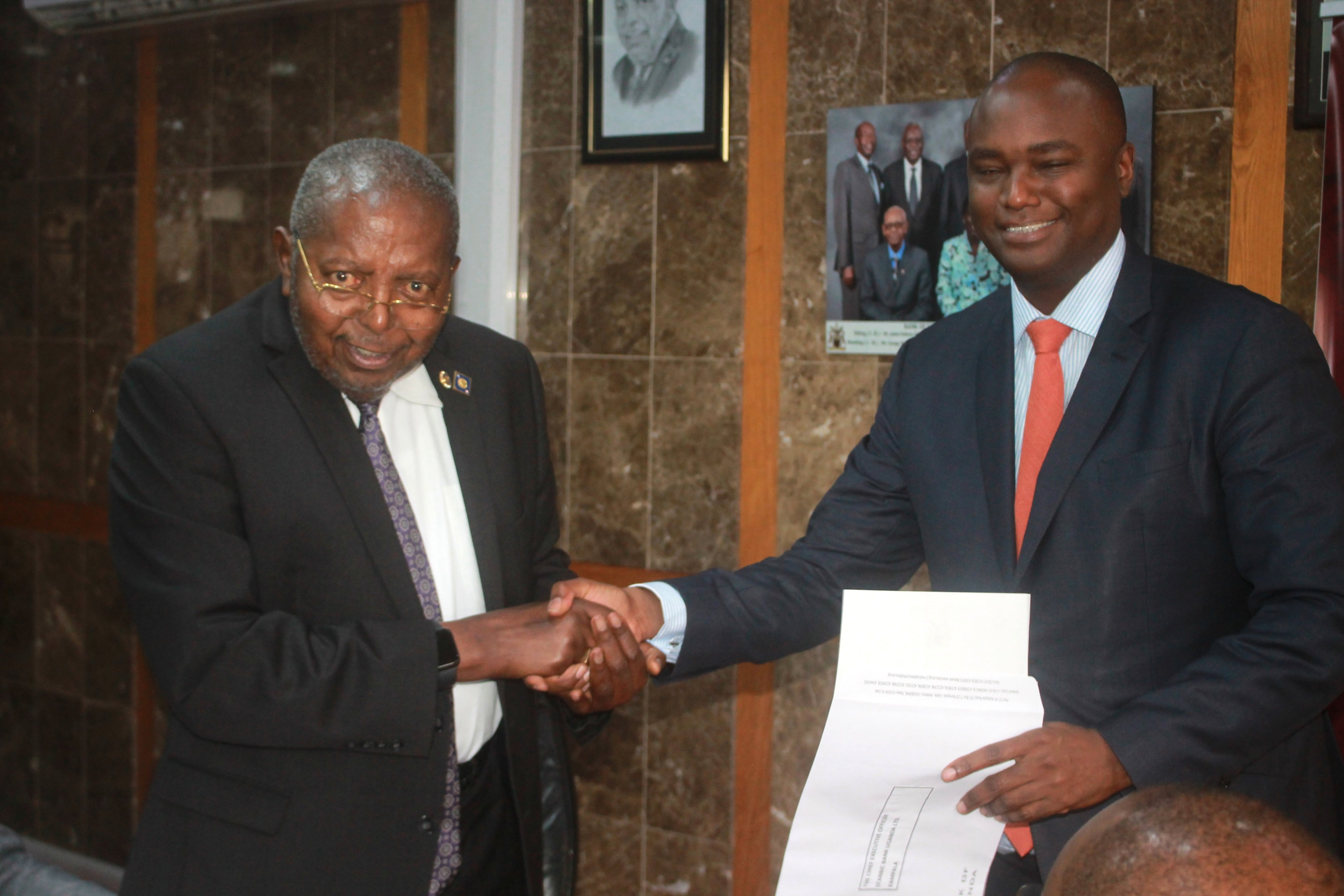 Central Bank governor Mutebile shakes hands with Stanbic Chief Executive Patrick Muhairwe. (PHOTO/Courtesy)