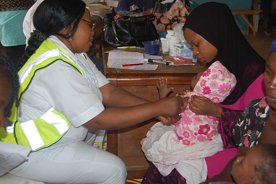 Nurse Onwunata administering a vaccine to a child at Dutse Alhaji PHC, Abuja