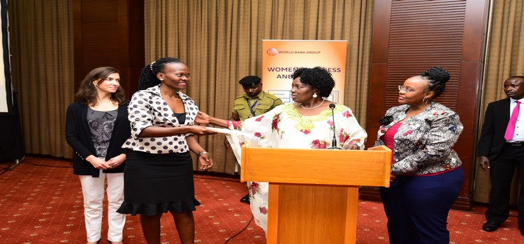 Speaker Kadaga gives certificates to one of the performers in the women interprenual workshop
