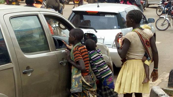 Street kids begging for money in Kampala traffick jam