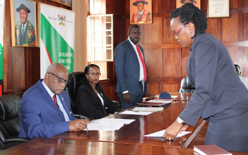 Justice John Patrick Mashongo Tabaro witnessing the swearing in of Dr. Phiona Muhwezi Mpanga- Representative of MUASA. Other members in the photo are; the Chairperson of Makerere University Council Mrs. Lorna Magara and the Acting University Secretary Mr. Yusufu Kiranda.