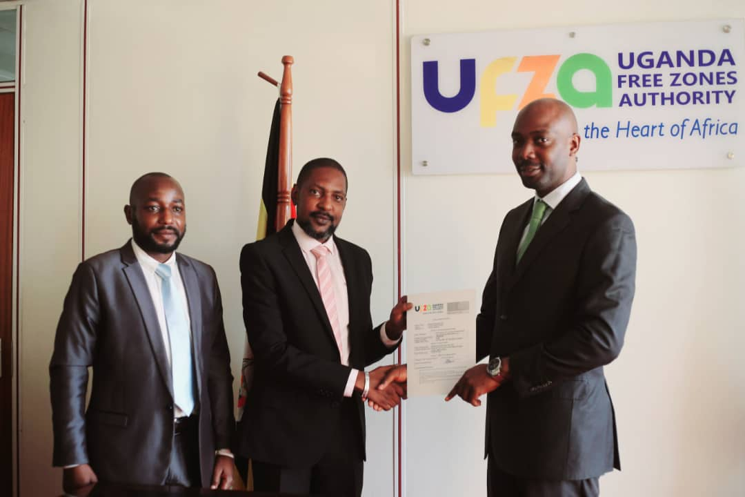 R-L: The Executive Director of Uganda Free Zones Authority, Mr Richard Jabo hands over a Free Zone Developer's Licence to Eng. Brian Kalibbala and Eng. Boney Ntambi of M/S Kimsam Investments Ltd at UFZA offices