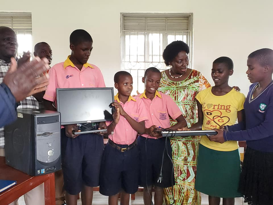 Speaker Rebecca Kadaga in a photo with pupils holding some of the computers she donated on Saturday