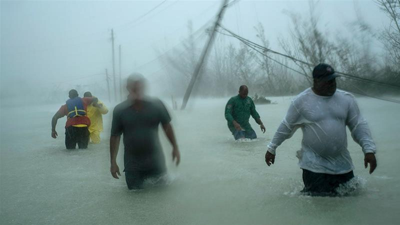 olunteers walk under the wind and rain of Hurricane Dorian, on a flooded road after rescuing several families that arrived on small boats, near the Causarina bridge in Freeport, Grand Bahama, Bahamas