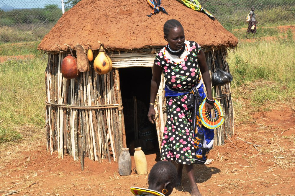A pokot woman in Amudat coming out of her house she built to represent their traditional houses during Karamoja culture day (photo by Jonathan Opolot)
