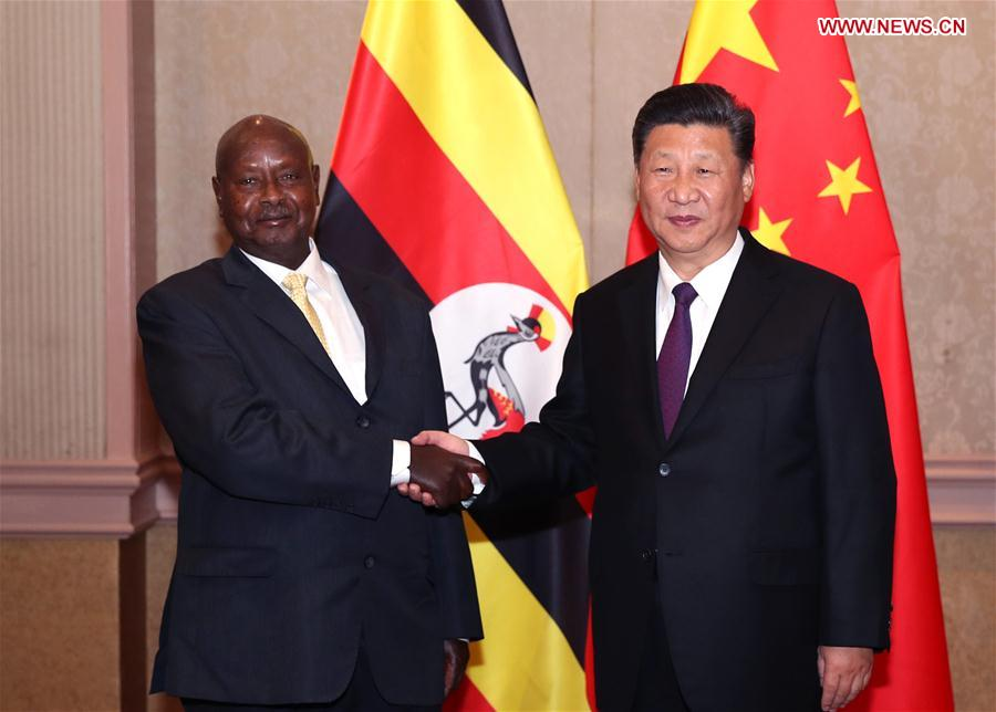 Chinese President Xi Jinping (R) meets with his Ugandan counterpart Yoweri Museveni