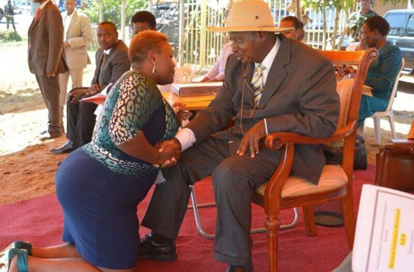 Singer Kusasira kneels before President Museveni (PHOTO/File)